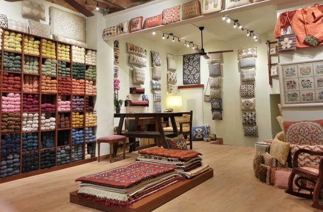 Recepción de la tienda de Talleres de Cañamazo con alfombras, cojines y lanas expuestas